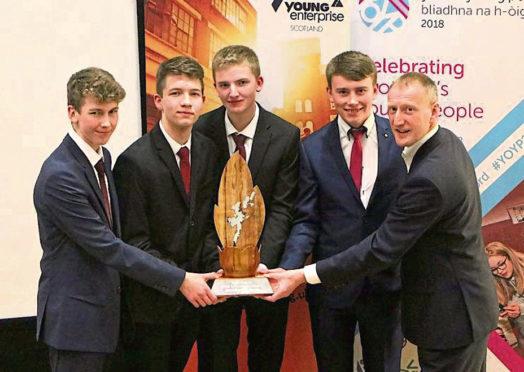 Left to Right: Shetland Gift Company members Scott Smith, Jack Irvine, Cameron Andrews, Michael Jamieson with local MSP Tavish Scott who presented the award. Photo: Stewart Hornal