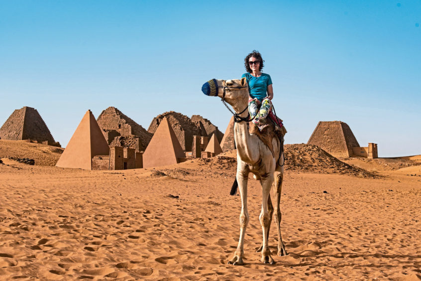 Sarah Marshall on a camel just outside the pyramids of Meroe