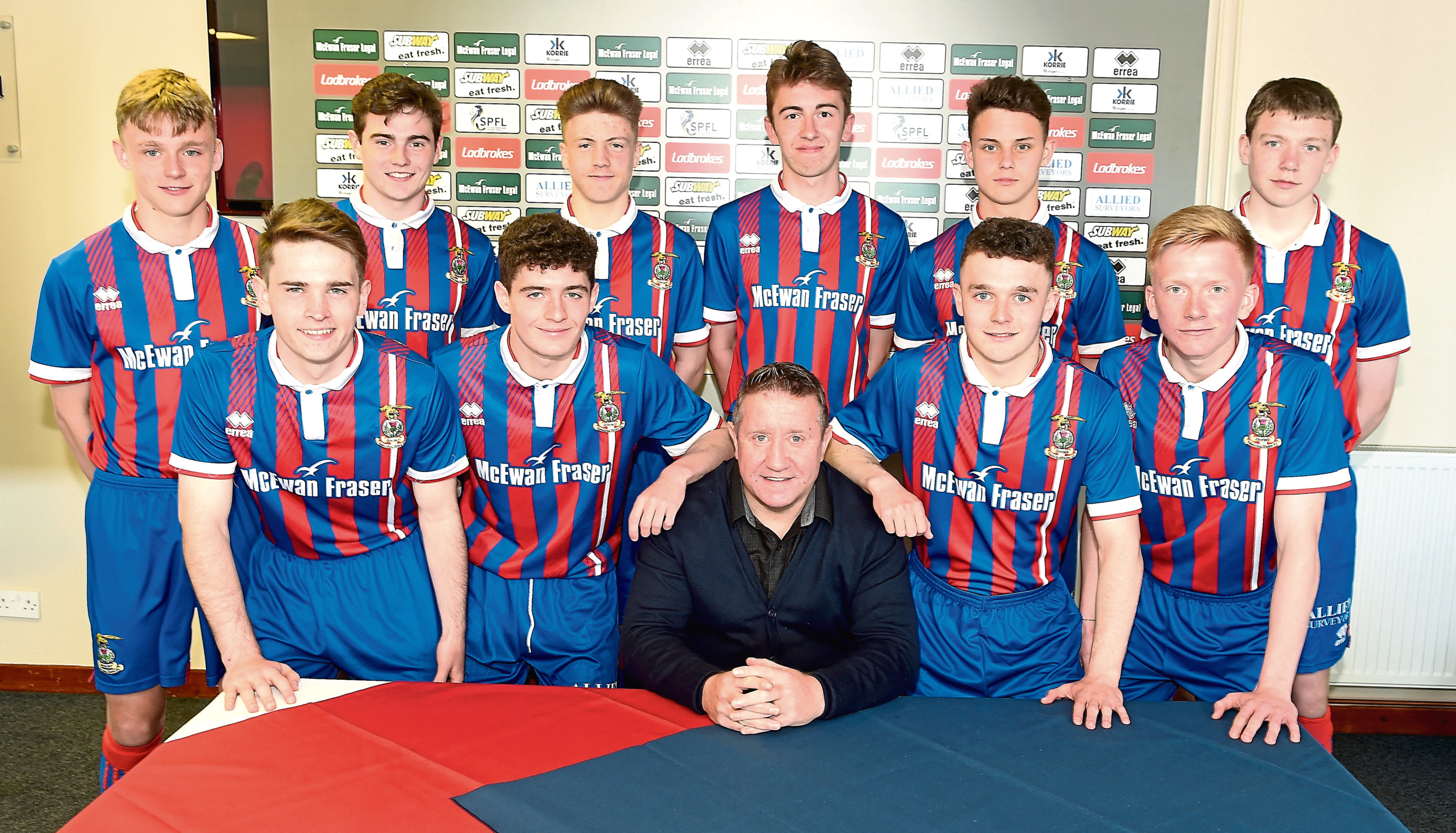 John Robertson with the 10 youngsters that signed their first professional deals with Caley Thistle.