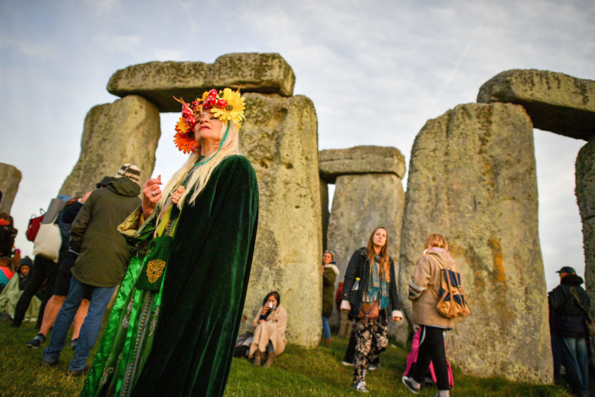 A woman wears a colourful head-dress at Stonehenge. Photo: Ben Birchall/PA Wire