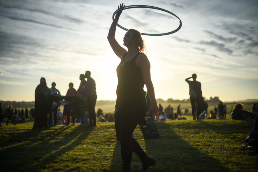 A woman twirls a hula-hoop as the sun rises at Stonehenge. Picture: Ben Birchall/PA Wire