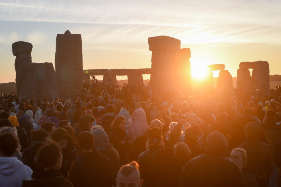 The sun breaks the horizon and shines through the stones at Stonehenge onto crowds of people celebrating the dawn of the longest day in the UK.  Picture: Ben Birchall/PA Wire