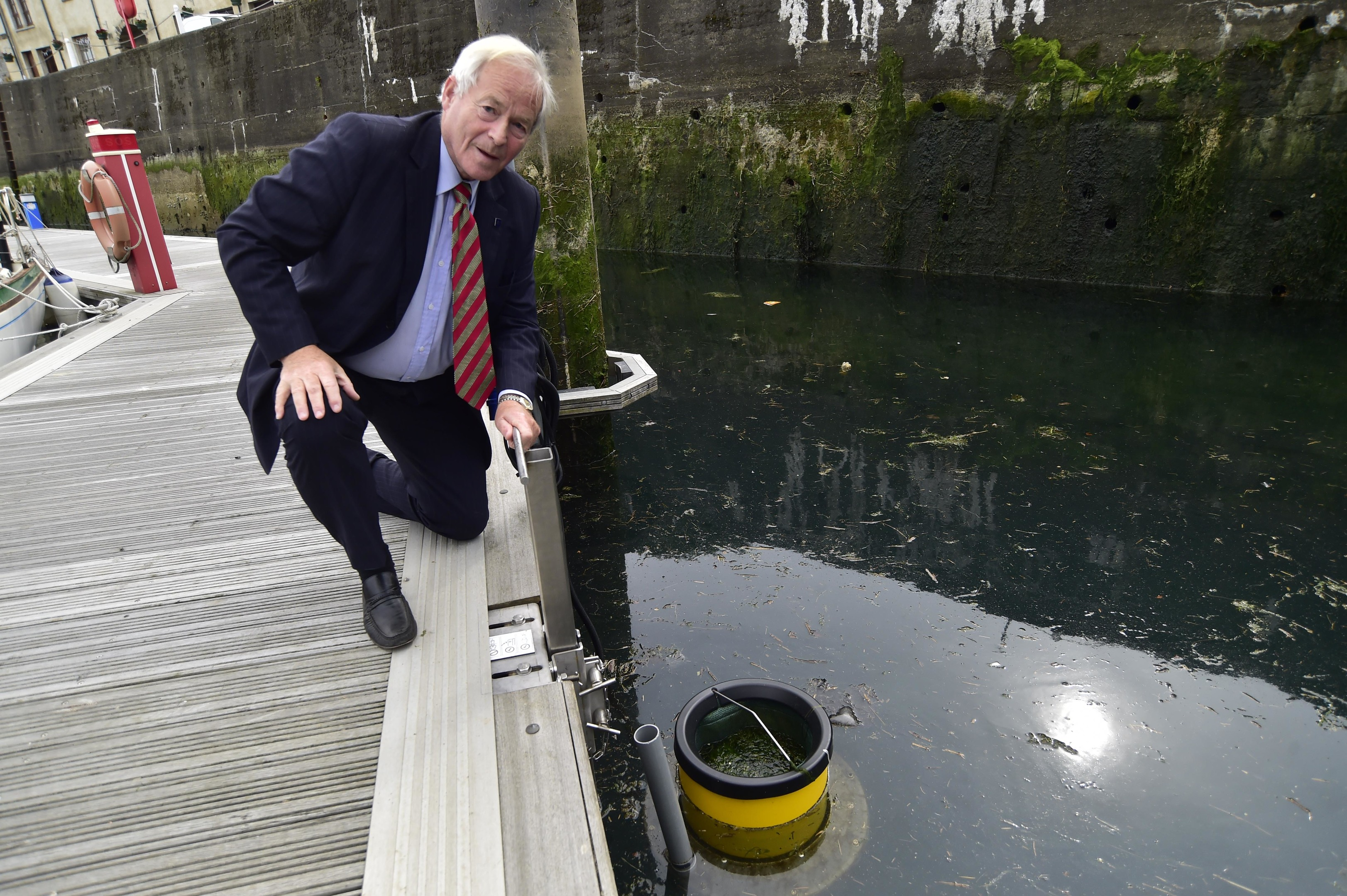 Councillor Mike Roy beside the new filter at Banff Marina.