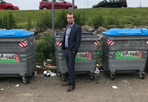 """SNP councillor Stephen Flynn standing at the """"disgusting"""" recycling point in Cove"""