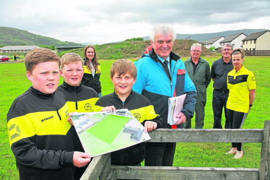 Brothers look over the plans for the new pitch at Fort William