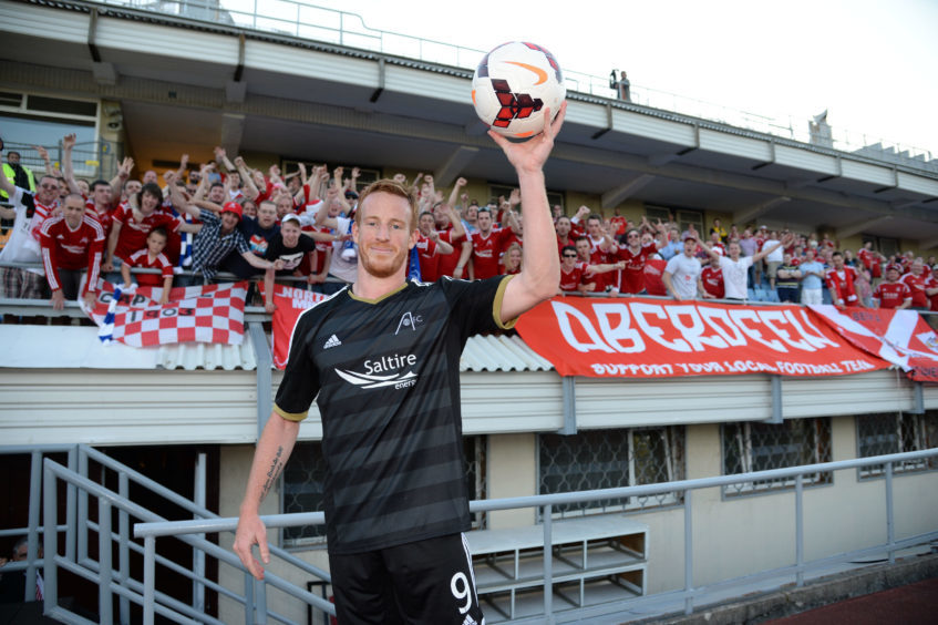 Rooney with the visiting Aberdeen fans and the match ball after scoring a hat-trick against Daugava Riga in Latvia in July 2014.