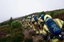 The trainee firefighters scaling Bennachie hill in Aberdeenshire.