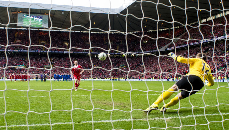 Rooney's penalty flies past Caley Thistke's Dean Brill to win the Dons the League Cup on March 16, 2014.