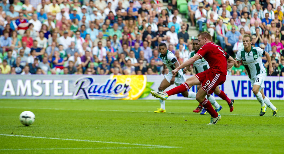 Adam Rooney fires his penalty home to give Aberdeen the lead against Groningen in the Europa League.