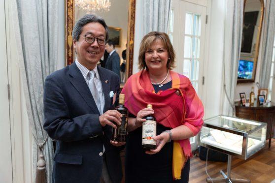Fiona Hyslop, holding a bottle of Ben Nevis with Nikka Whisky master blender Tadashi Sakuma.