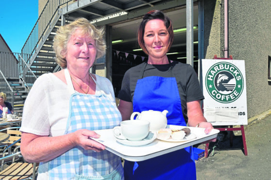 Volunteer Betty Jack, left, with support worker Ashley Runcie ready to serve customers at the cafe.