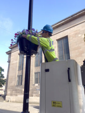 Teams from SSEN helped put up the flower baskets in Elgin town centre.