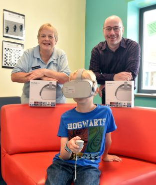 Alfie tries out the new games with the help of play specialist Helen MacCuish and Orion IT Director Duncan Murray.  Picture by COLIN RENNIE