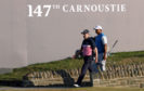 Russell Knox and Tiger Woods walk onto the 18th during day one of The Open at Carnoustie.
