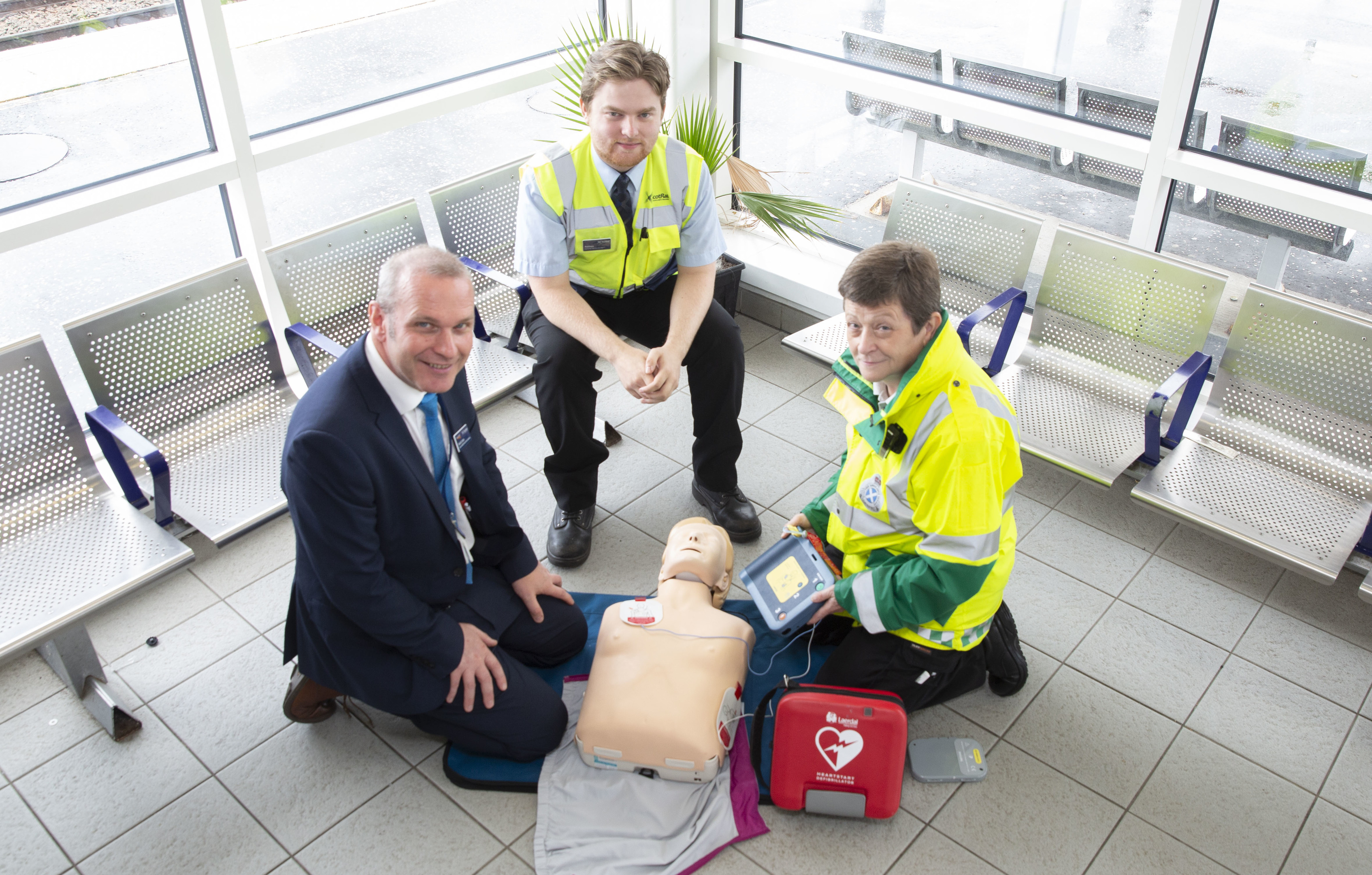 Karen Burns (right) demonstrates how to use a defibrillator to David Lister and Matthew Marshall.