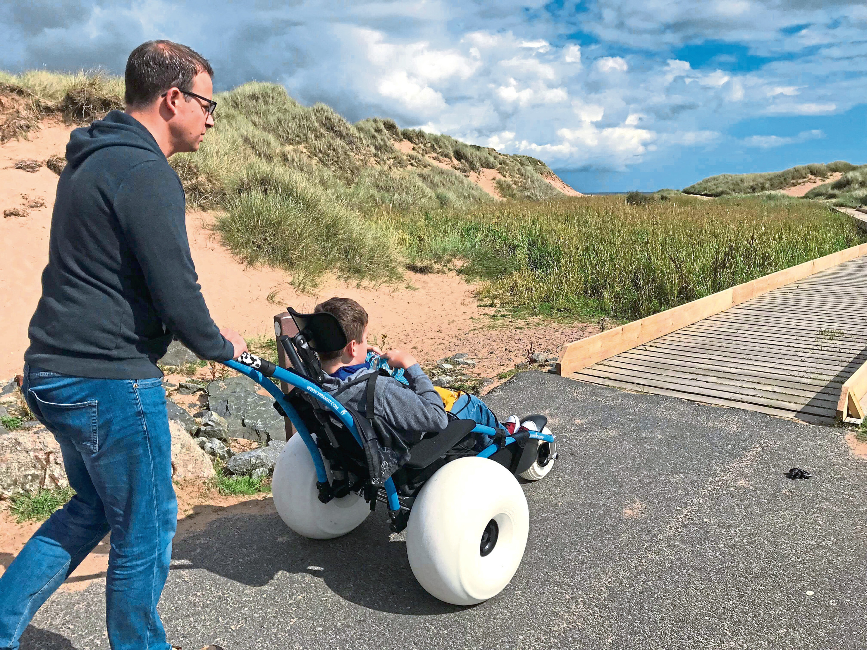 Ben Henry tries out the new Hippocampe wheelchair at Balmedie beach with father Gavin. Submitted