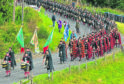 Clansmen march through the glen from Bellabeg, on their way to the Lonach Highland Gathering.