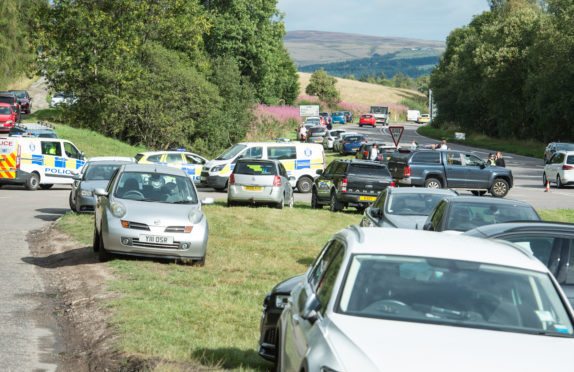 Cars park on the A941 Elgin road near Craigellachie in an attempt to reach the Macallan distillery.