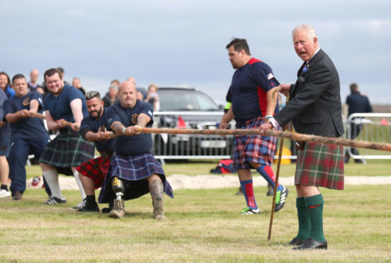 The Duke of Rothesay judging a tug-of-war competition.