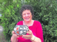Iona Nicol with the gift that may provide a windfall at the auction.