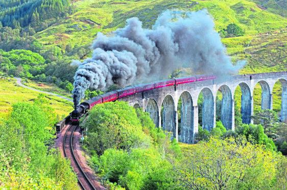 Steam train crossing the Glenfinnan Viaduct in Scotland.