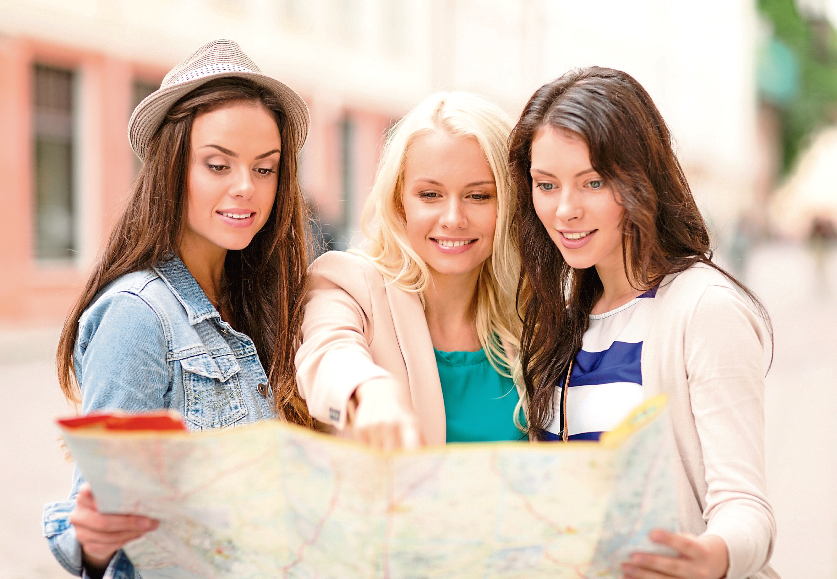 holidays and tourism concept - three beautiful girls looking into tourist map in the city