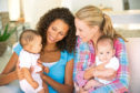 2209 Yourlife YL Health Two Young Mothers Sitting On Sofa With Babies At Home