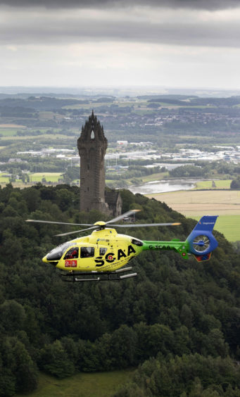 'Helimed 76' is pictured flying over The National Wallace Monument in Stirling.