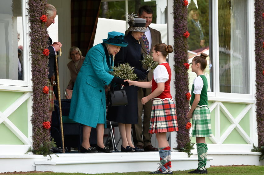 Braemar Gathering 2018, at The Princess Royal and Duke of Fife Memorial Park in Braemar. Picture of the Queen and Princess Anne receiving flowers from (L-R) Esme Evans, 11, and Fern Jolly, 10.  Picture by KENNY ELRICK     01/09/2018