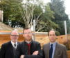 Sam Andrew (centre) of Ashley Road, in his back garden, with councillors John Cooke (left) and Martin Greig, showing the height of the overgrown trees of his neighbour which block out light to his garden and the rear of his house.
