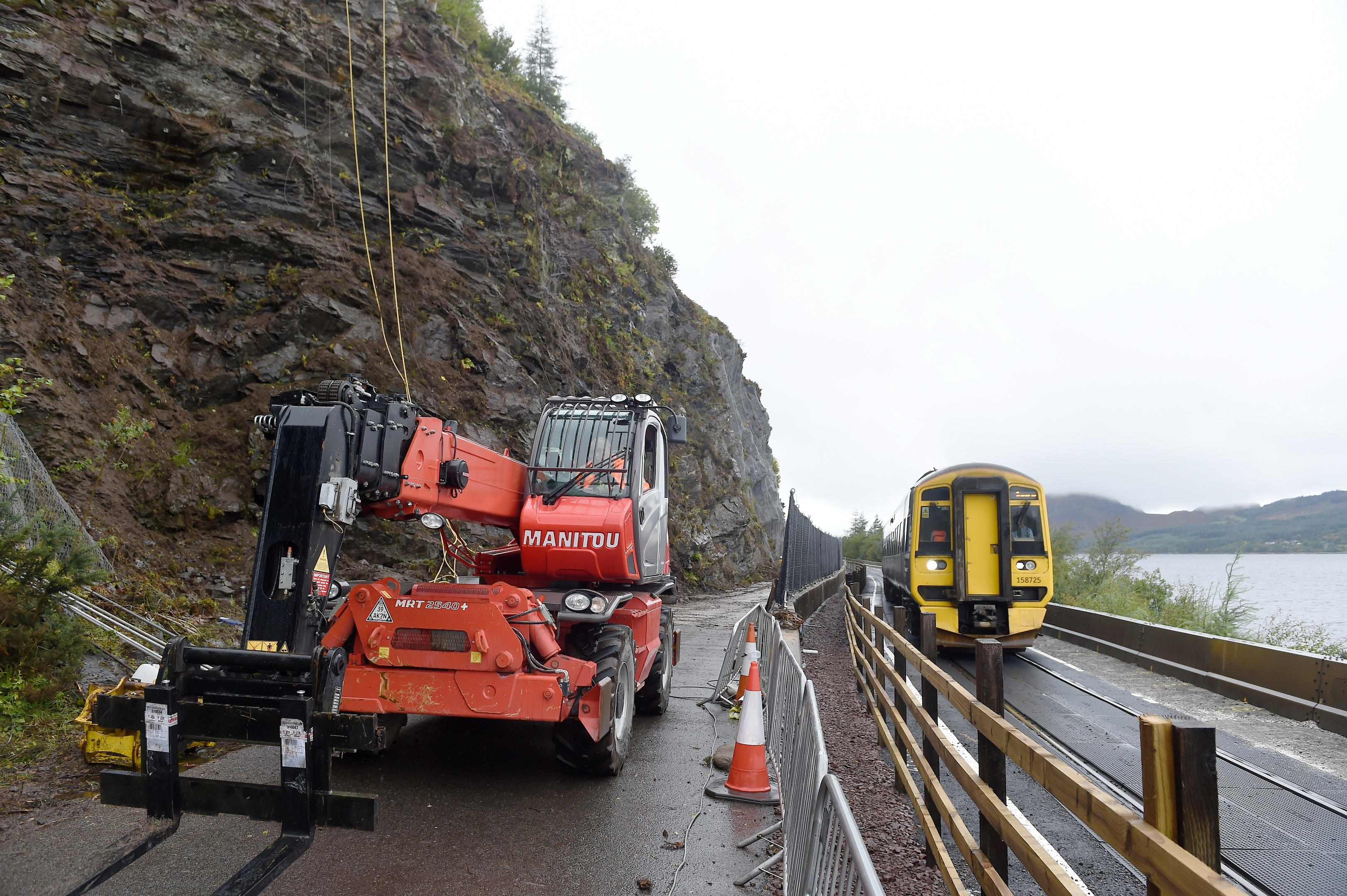 Engineers work high above the road last year as a train from Kyle passes works on the A890 Stromeferry bypass. Picture by Sandy McCook
