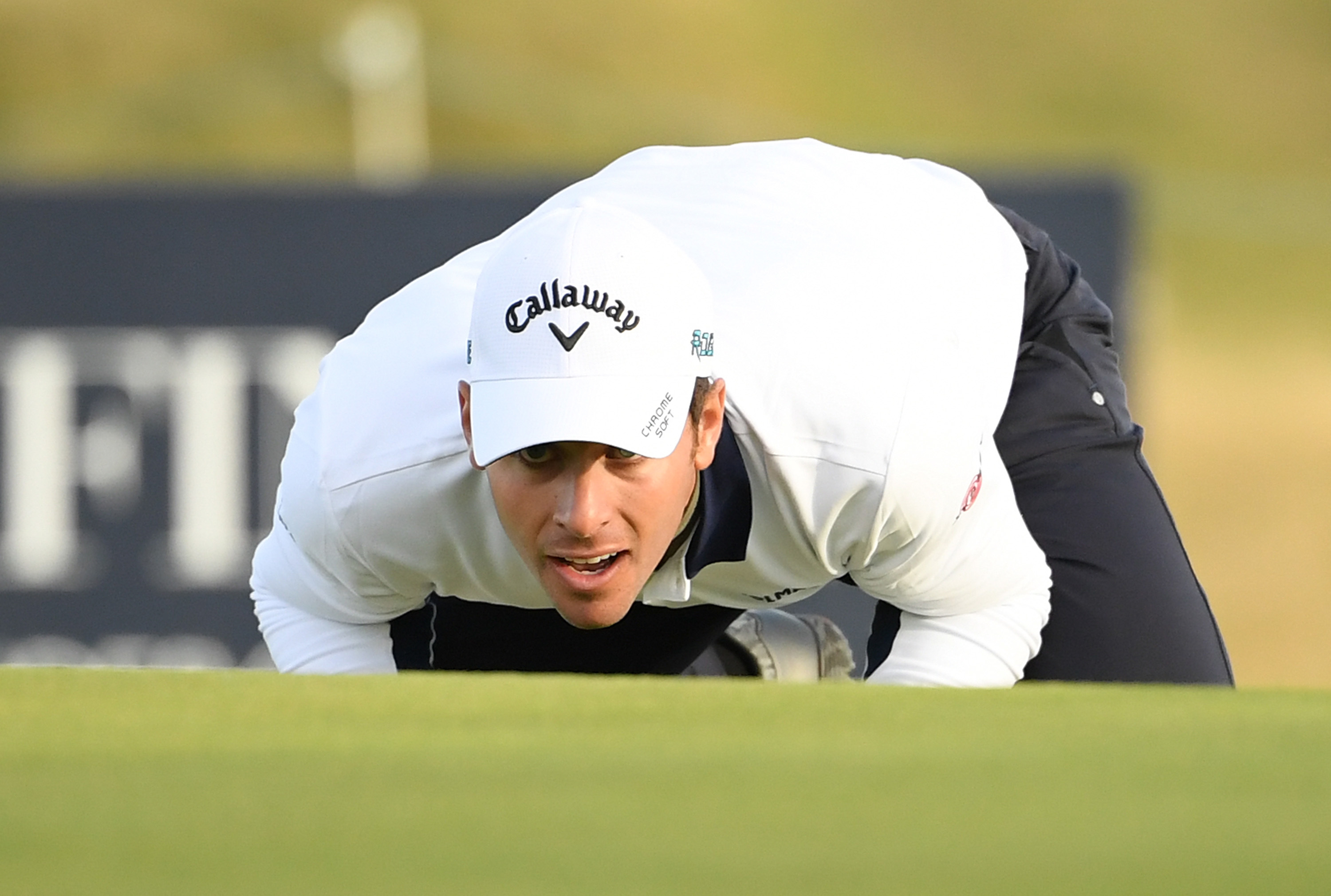 Andrea Pavan of Italy lines up a putt on the ninth green