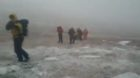 Mountain rescue teams battling snowy conditions.