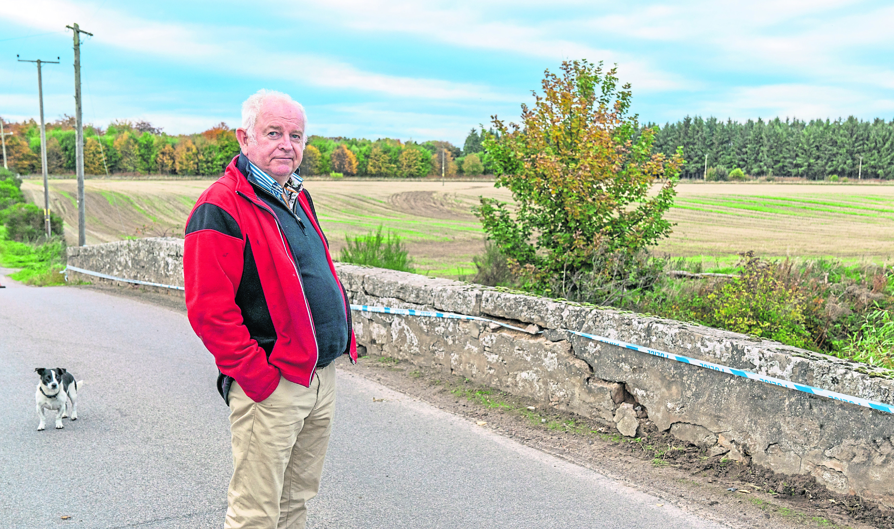 George Elder next to the damaged bridge over the Muckle Burn next to his Farm at Brodie,