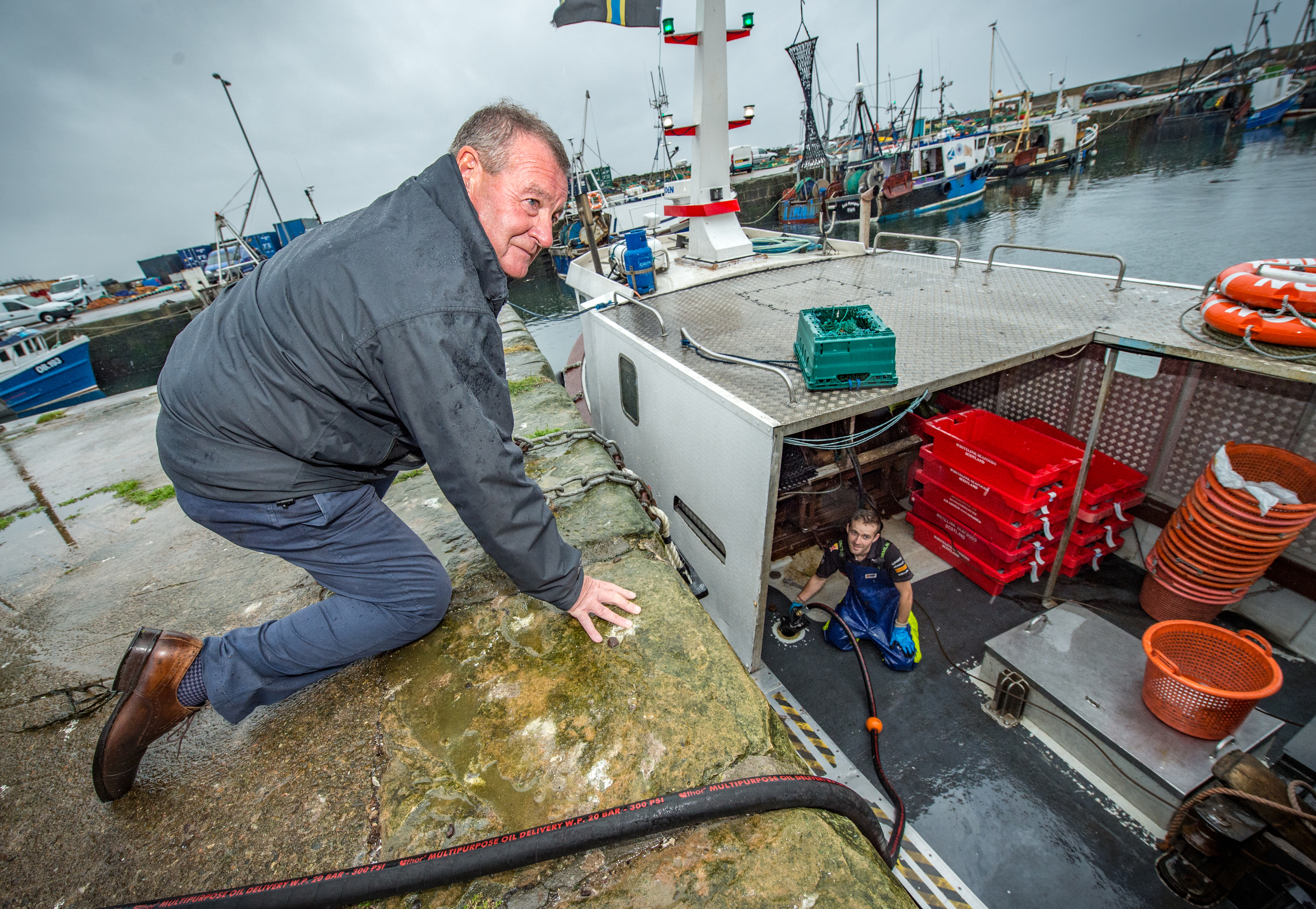 Hamish McPherson and a fisherman fuelling a boat.