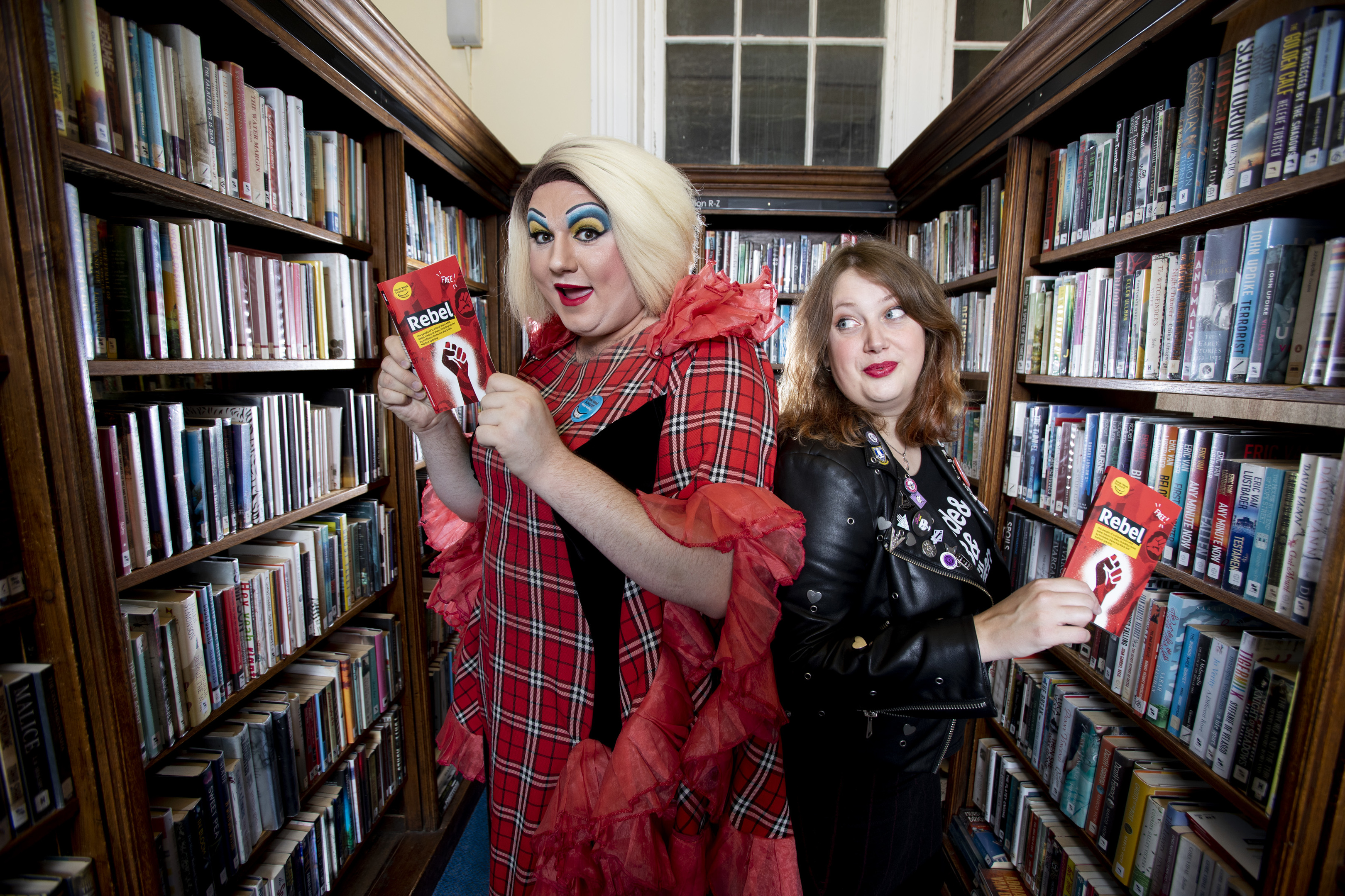 PROGRAMME LAUNCH OF BOOK WEEK SCOTLAND 2018 Book Week Scotland 2018 runs from 19 November to 25 November Pictured Drag Queen Nancy Clench with author Claire Askew holding  the Book Week Scotland Rebel Book at The Edinburgh Central Library.  The programme for Scotland's seventh national celebration of books and reading was launched today, Wednesday 3 October, with a photocall of rebellious librarians held at Central Library, Edinburgh. Drag queen and Book Week Scotland ambassador, Nancy Clench, and bestselling author Claire Askew posed with copies of the Rebel book, which features a story from herself, as well as others submitted from the public. Working with a wide range of partners, Scottish Book Trust – the national charity changing lives through reading and writing – will deliver events and activities across the country during Book Week Scotland 2018, which runs from 19 November to 25 November, linked to this year's theme of Rebel. There are hundreds of free events taking place across many different local authorities, funded by Scottish Library and Information Council (SLIC). Authors holding events include: bestselling YA writer and activist Juno Dawson; crime writer Ann Cleeves and outdoors expert and broadcaster Cameron McNeish. Rebel Book Free copies of the Rebel book can be ordered via Scottish Book Trust's website. 100,000 copies have been printed and the book will also be available from libraries across Scotland during Book Week. The book contains 40 stories, including work from: bestselling author Sara Sheridan; playwright and performer Jo Clifford; Book Week Scotland ambassador and forensic anthropologist Professor Dame Sue Black, and Gaelic writer David Eyre. An ebook and audiobook version of Rebel will also be downloadable from Scottish Book Trust's website. Scottish Book Trust has once again partnered with Royal National Institute    Photograph by Martin Shields  Tel 07572 457000 www.martinshields.com © Martin Shields