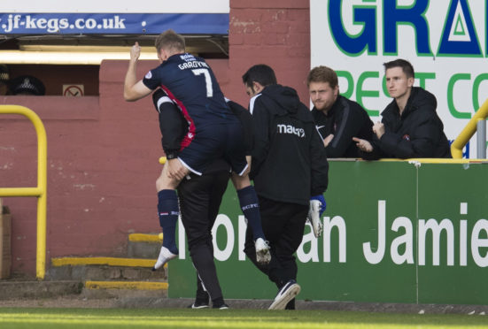 Ross County's Michael Gardyne is carried down the touchline against Dundee United.