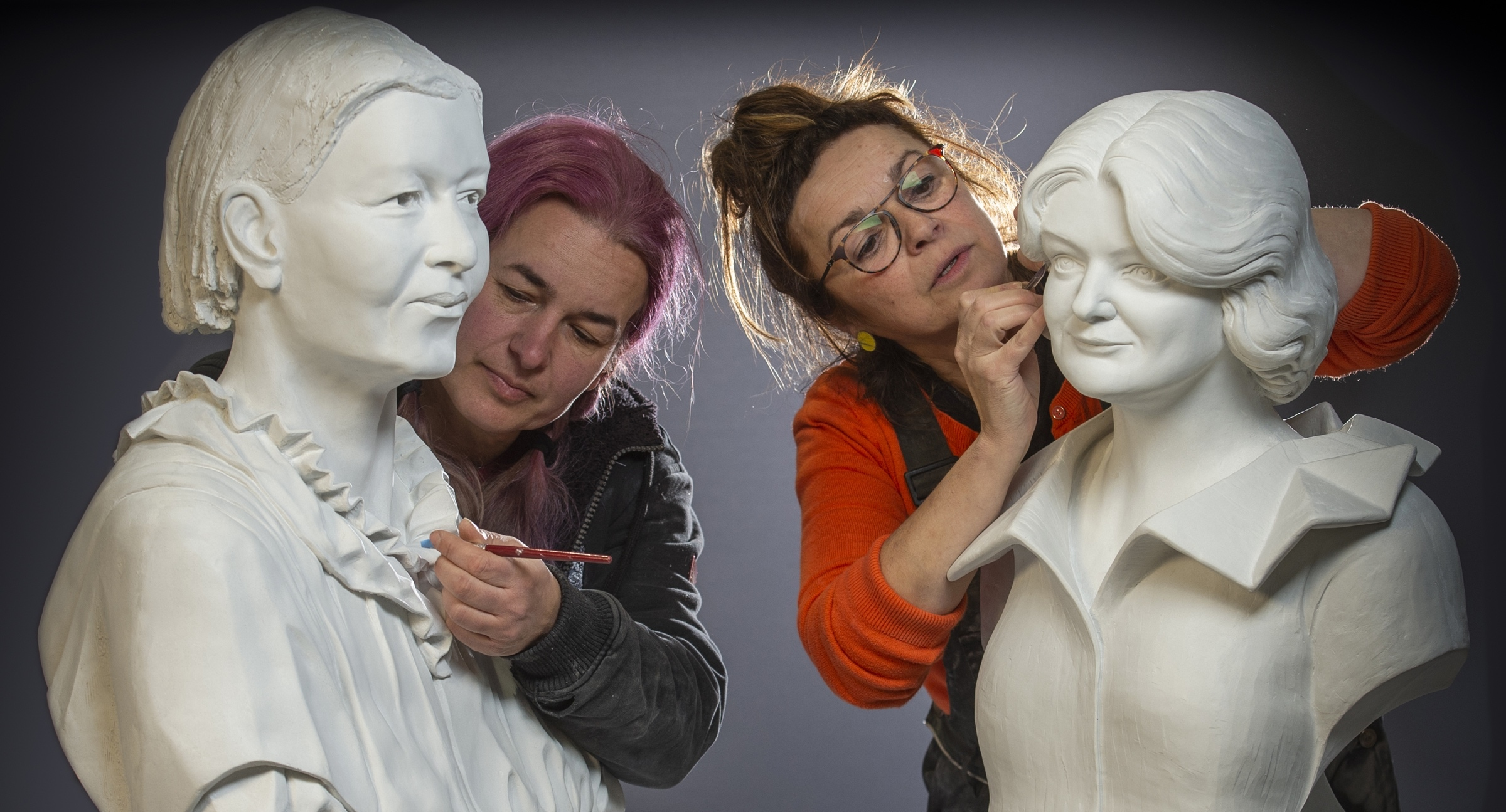 Sculptors Csilla Karsay and Graciela Ainsworth add the finishing touches to the busts of Mary Slessor and Maggie Keswick Jencks.