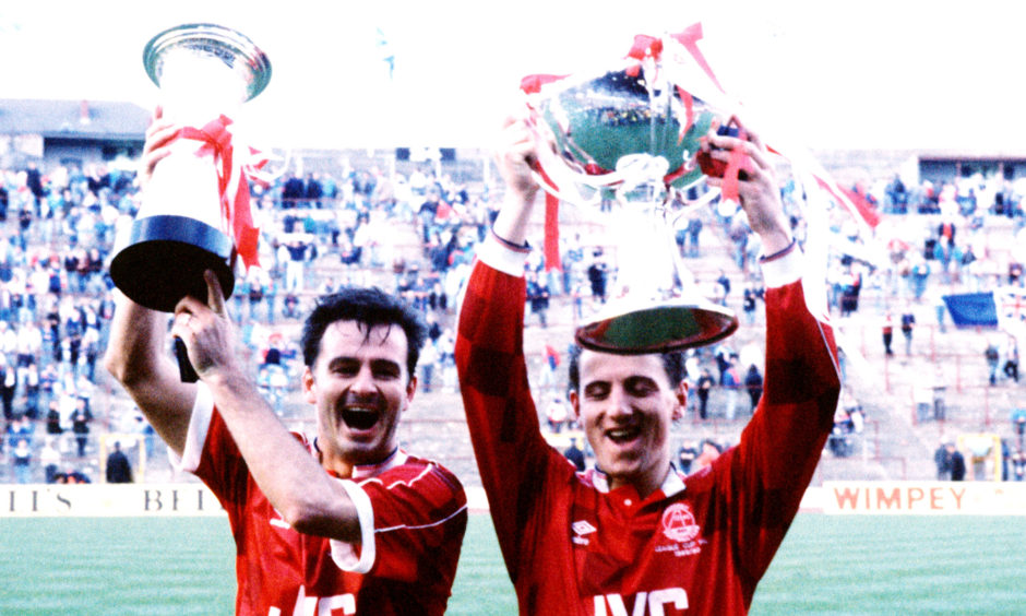 Aberdeen's Charlie Nicholas (left) holds the Skol Cup trophy and Paul Mason holds the League Cup trophy after their victory.