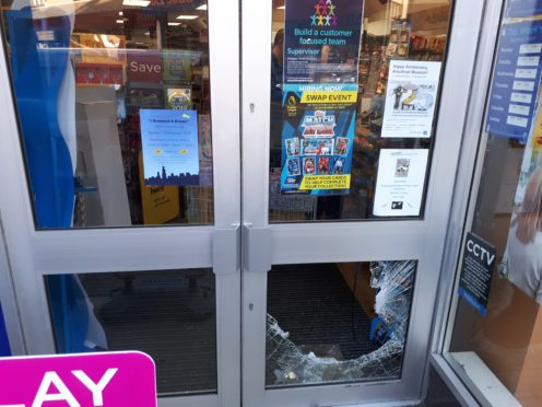 Damage to the door of W H Smith on Marischal Street, Peterhead, where the collection tins were allegedly stolen.