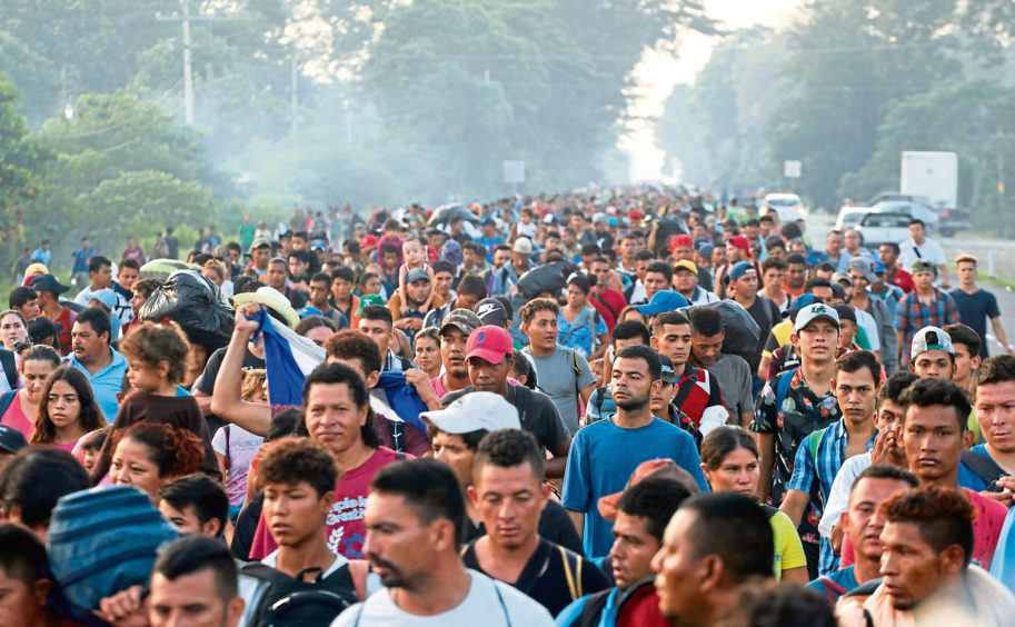 Central American migrants walking to the U.S. start their day departing Ciudad Hidalgo, Mexico, Sunday, Oct. 21, 2018. Despite Mexican efforts to stop them at the border, about 5,000 Central American migrants resumed their advance toward the U.S. border early Sunday in southern Mexico. Their numbers swelled overnight and at first light they set out walking toward the Mexican town of Tapachula. (AP Photo/Moises Castillo)