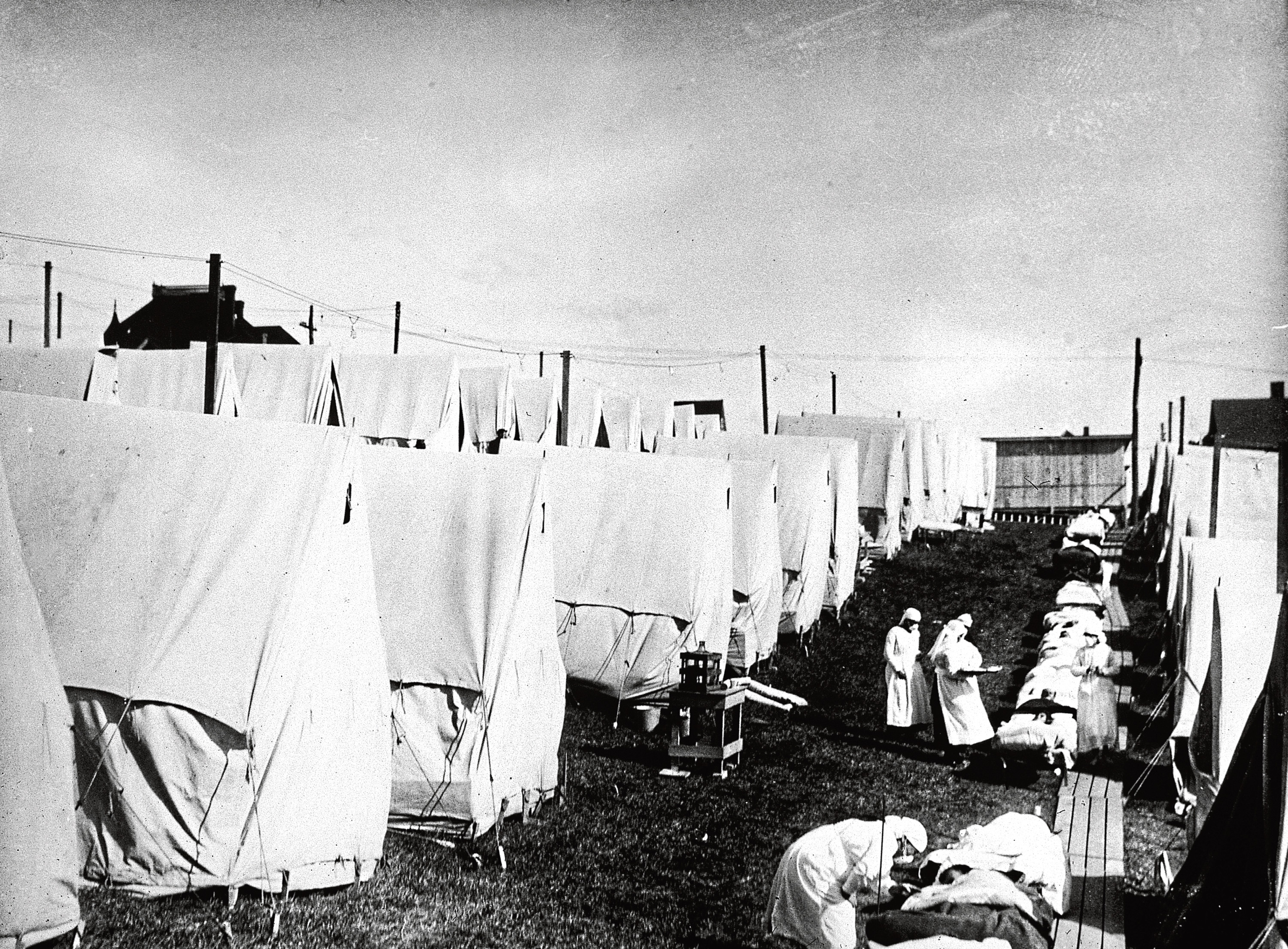 Nurses care for victims of a Spanish influenza epidemic outdoors.