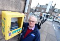 Stonehaven Community Council Chairman Raymond Christie at the defibrillator.