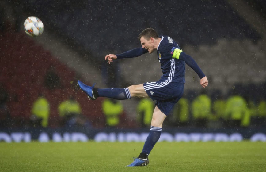 Captain Andy Robertson kicks the ball in celebration at full time