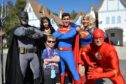 Alex Crichton posting with superheroes at Disney World in Florida