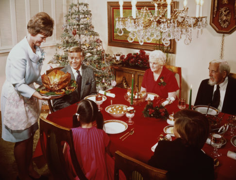 A mother bringing a large turkey to the table for Christmas dinner, circa 1965. (Photo by L. Willinger/FPG/Hulton Archive/Getty Images)