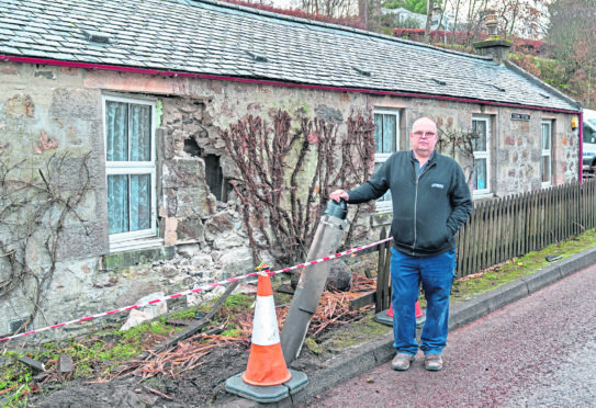 Kevin at the damaged part of his home and demolished lampost.