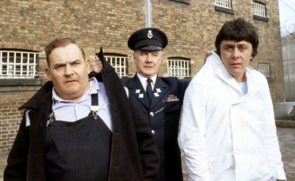 """Ronnie Barker, Richard Beckinsale and Fulton Mackay during location shooting for the film version of their TV series """"Porridge"""" at Chelmsford Jail."""