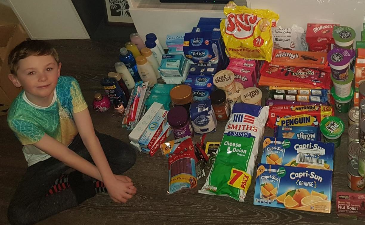 Riley Winton, age 10, with some of the food and essentials he donated to the homeless