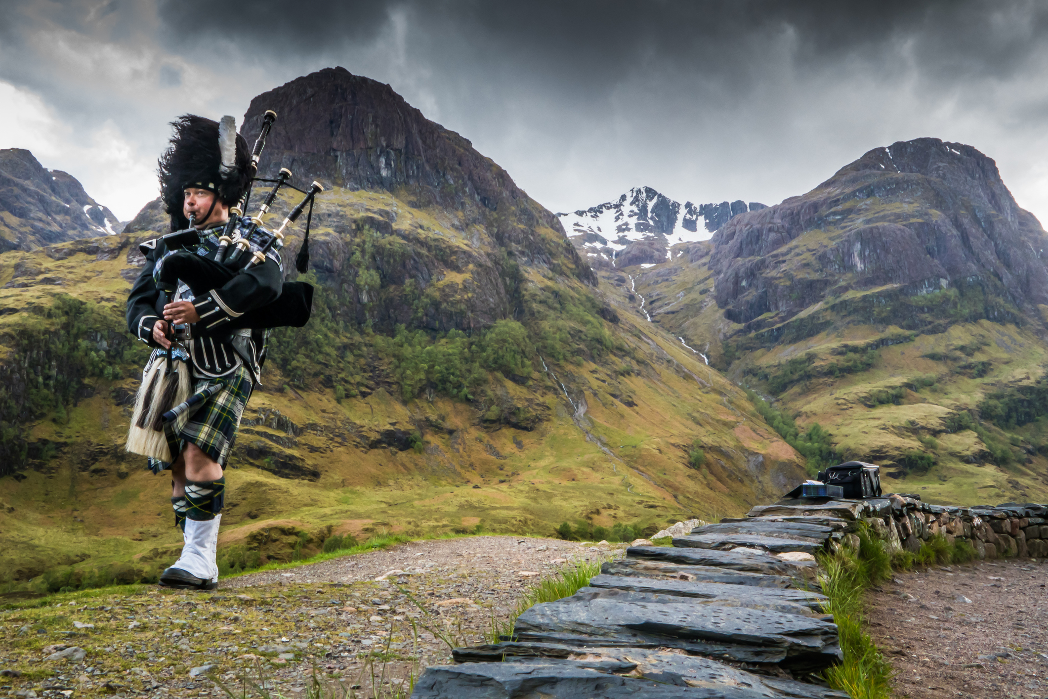 Traditional bagpiper in the scottish highlands by Glencoe